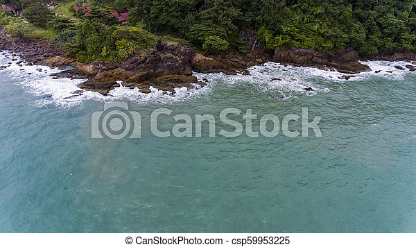 Aerial view of a rocky and green beach shore. - csp59953225
