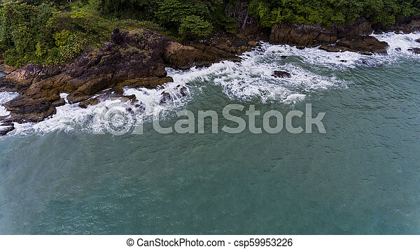 Aerial view of a rocky and green beach shore. - csp59953226