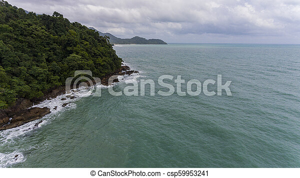 Aerial view of a rocky and green beach shore. - csp59953241