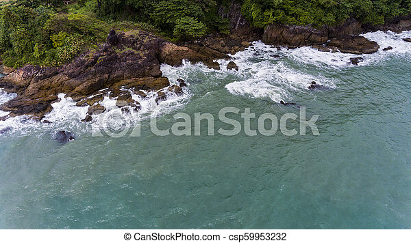 Aerial view of a rocky and green beach shore. - csp59953232