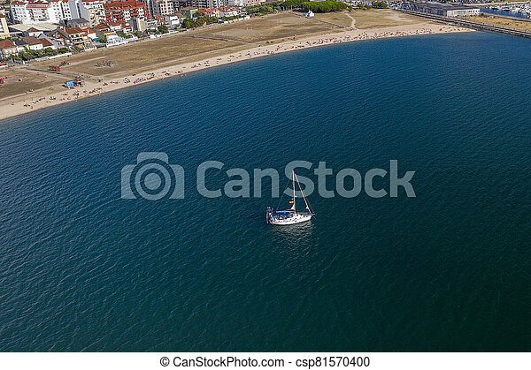 aerial view of a white sailboat in front of a sandy beach - csp81570400