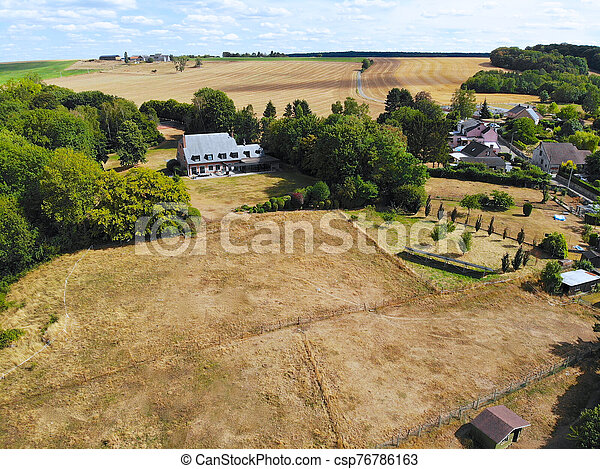 Aerial view of agriculture farmland and and small house during dry summer season - csp76786163