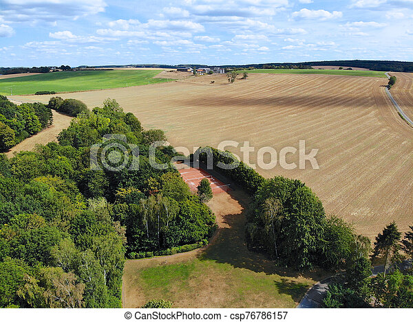 Aerial view of agriculture farmland and and small house during dry summer season - csp76786157