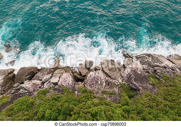 Aerial view of beautiful ocean waves and rocky coast with greenery - csp70896003
