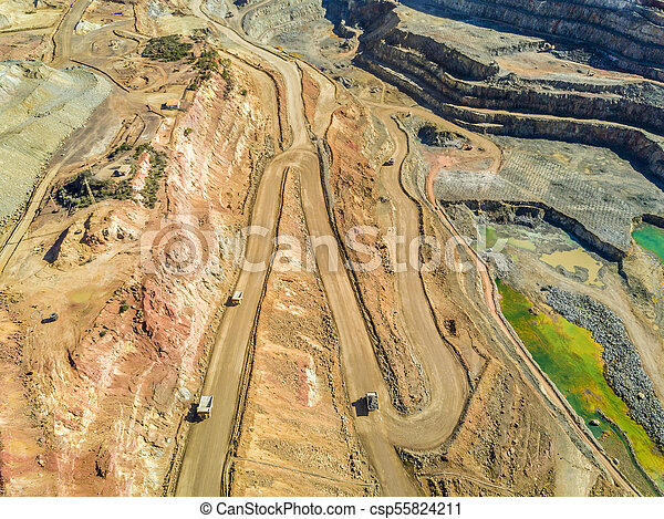 Aerial view of big trucks in huge, open pit mine - csp55824211