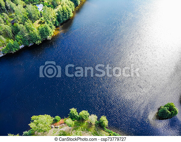 Aerial view of blue lake and green forest on a sunny summer day in Finland. Drone photography - csp73779727