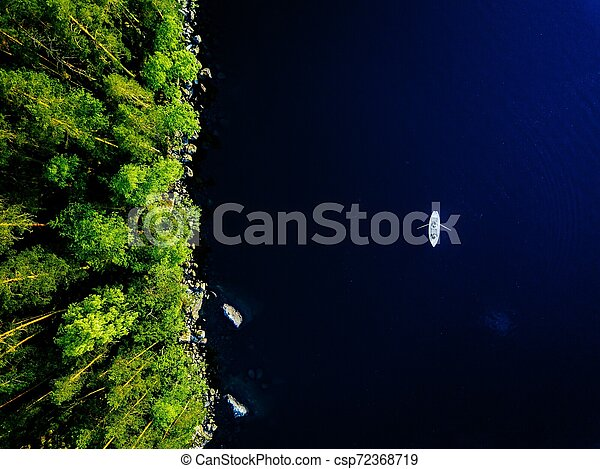 Aerial view of blue lake with a fishing boat and green forests with rocks in Finland. - csp72368719