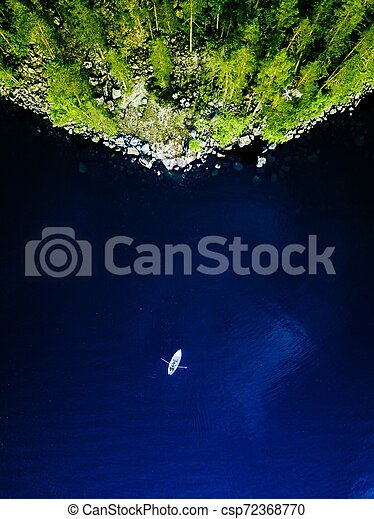 Aerial view of blue lake with a fishing boat and green forests with rocks in Finland. - csp72368770
