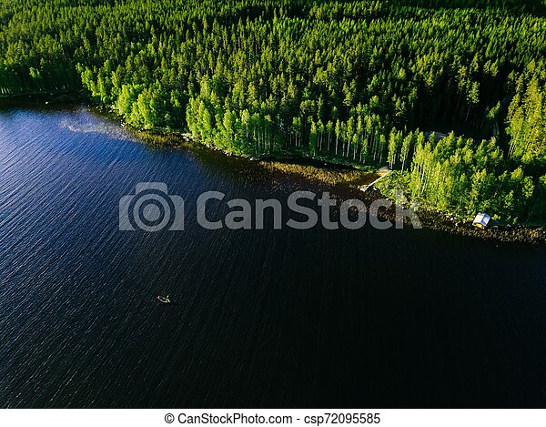 Aerial view of blue lake with a fishing boat and green woods on a sunny summer day in Finland. - csp72095585