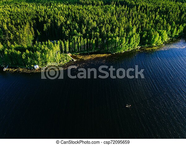 Aerial view of blue lake with a fishing boat and green woods on a sunny summer day in Finland. - csp72095659
