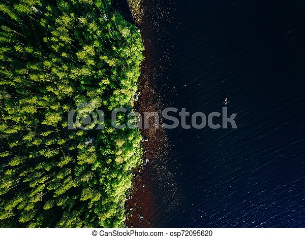Aerial view of blue lake with a fishing boat and green woods on a sunny summer day in Finland. - csp72095620