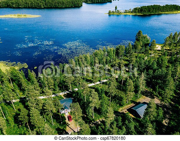 Aerial view of blue lake with green forests in Finland. Wooden house, sauna, boats and fishing pier by the lake. - csp67820180
