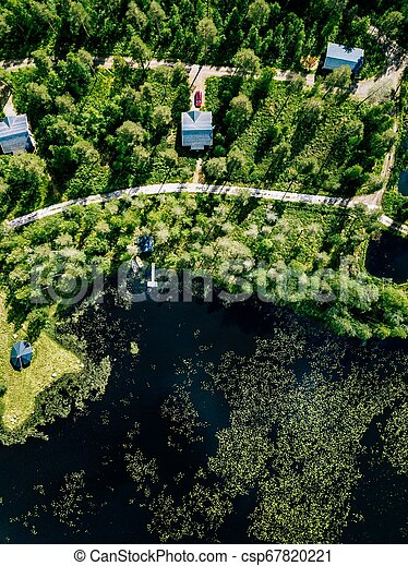 Aerial view of blue lake with green forests in Finland. Wooden house, sauna, boats and fishing pier by the lake. - csp67820221