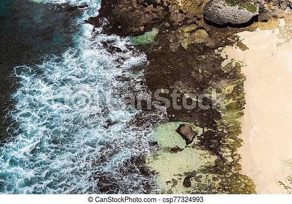 Aerial view of blue ocean waves crashing into rocky coast - csp77324993