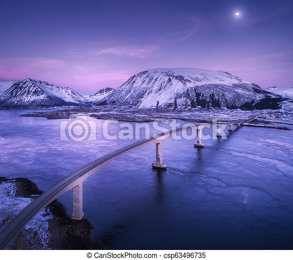 Aerial view of bridge, snow covered mountains, purple sky - csp63496735