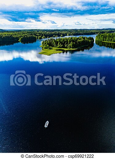 Aerial view of fishing boat in blue lake landscape with green forests on a sunny summer day in Finland. - csp69921222