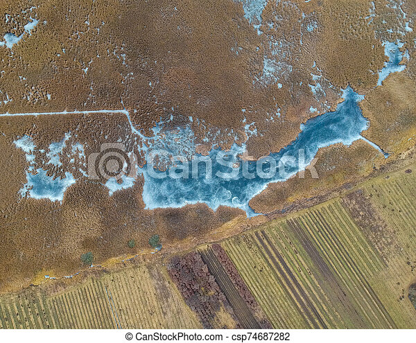 Aerial view of frozen lake in Hungary - csp74687282