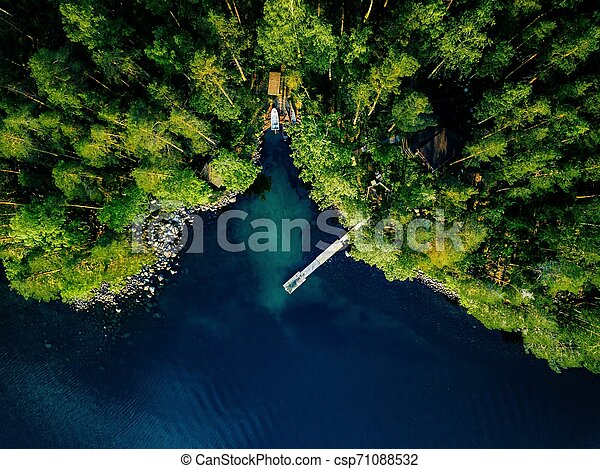 Aerial view of green forest, blue lake and wooden pier with boats in Finland. - csp71088532