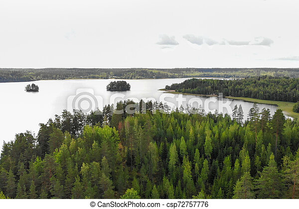 Aerial view of lake with island and forest on a summer cloudy day in Finland. Drone photography - csp72757776