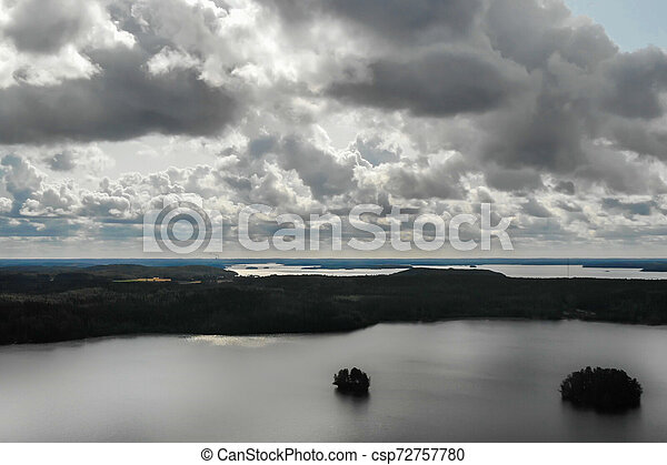 Aerial view of lake with island and forest on a summer cloudy day in Finland. Drone photography - csp72757780