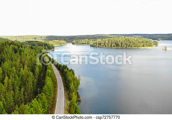Aerial view of lake with island, road and forest on a summer sunny day in Finland. Drone photography - csp72757770