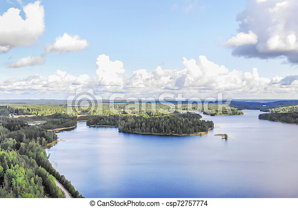 Aerial view of lake with island, road and forest on a summer sunny day in Finland. Drone photography - csp72757774