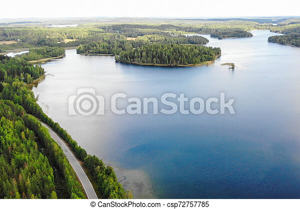 Aerial view of lake with island, road and forest on a summer sunny day in Finland. Drone photography - csp72757785