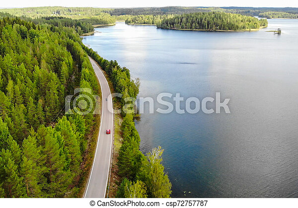 Aerial view of lake with island, road and forest on a summer sunny day in Finland. Drone photography - csp72757787