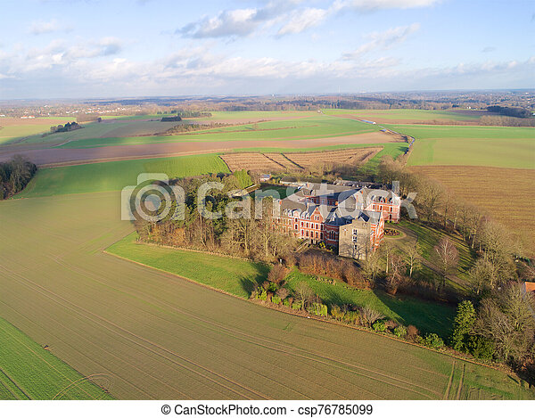 Aerial view of little farm castle surrounded by agriculture farmland et small forest - csp76785099