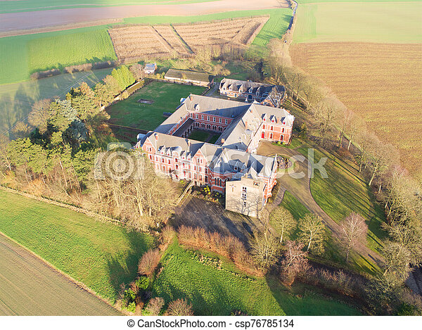 Aerial view of little farm castle surrounded by agriculture farmland et small forest - csp76785134