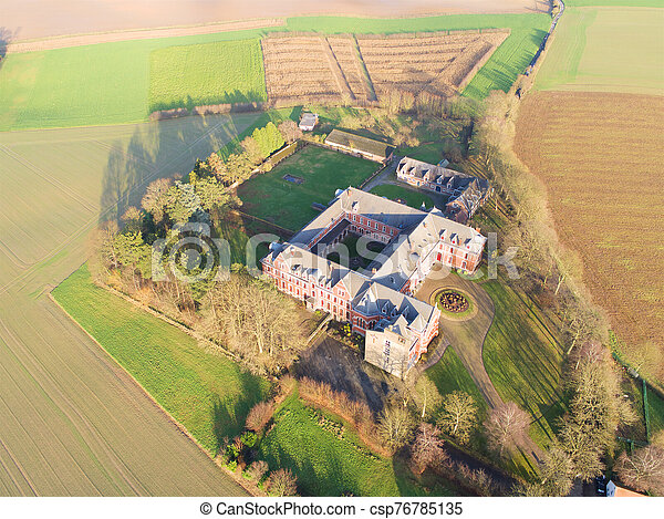 Aerial view of little farm castle surrounded by agriculture farmland et small forest - csp76785135