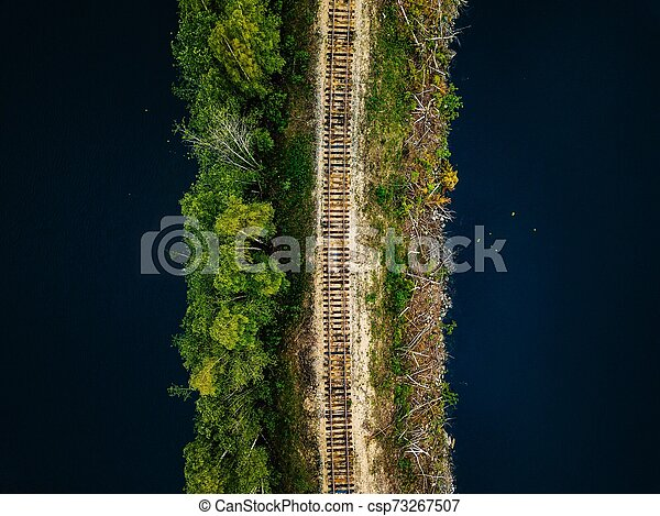 Aerial view of railroad tracks with green forest and blue lake in Finland - csp73267507
