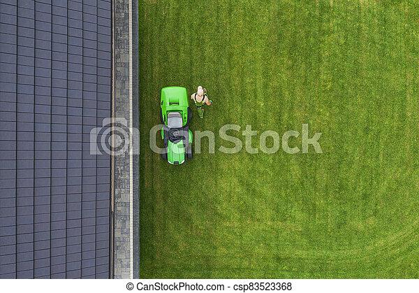 Aerial View of Riding Lawn Mower and Caucasian Gardener. - csp83523368