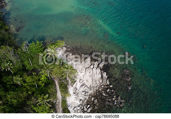 Aerial view of rocky shore with turquoise sea water and tropical green trees - csp78695088