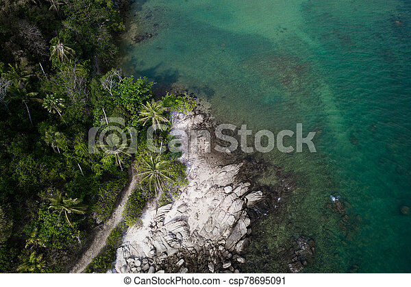 Aerial view of rocky shore with turquoise sea water and tropical green trees - csp78695091