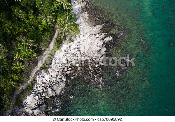 Aerial view of rocky shore with turquoise sea water and tropical green trees - csp78695092