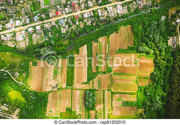 Aerial View Of Vegetable Gardens In Small Town Or Village. Skyline In Summer Evening. Village Garden Beds In Bird's-eye View - csp91202010