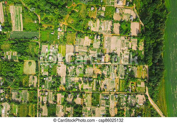 Aerial View Of Vegetable Gardens In Small Town Or Village. Skyline In Summer Evening. Village Garden Beds In Bird's-eye View - csp86025132