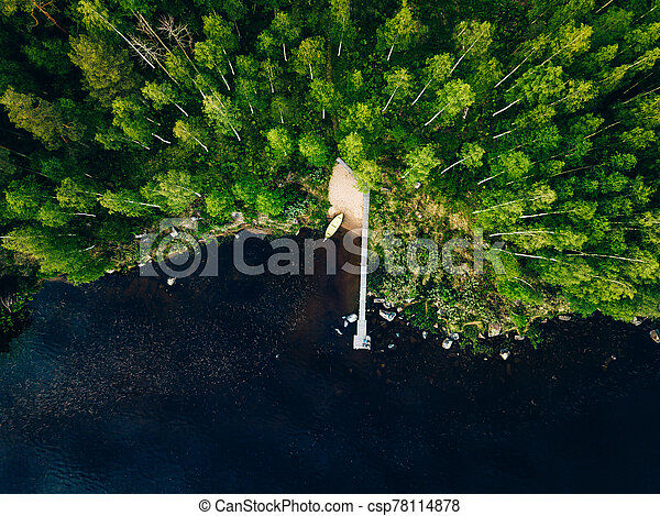 Aerial view of wooden pier with fishing boat on blue lake with green forest in Finland. - csp78114878