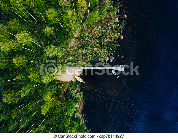 Aerial view of wooden pier with fishing boat on blue lake with green forest in Finland. - csp78114927