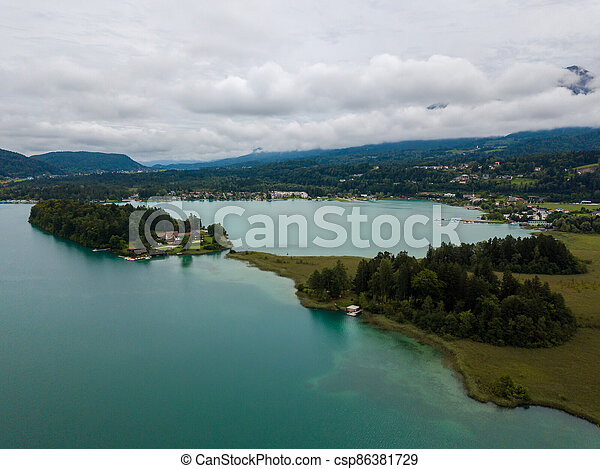 Aerial view on Lake 'Faaker See' in Carinthia (Kaernten), Austria with its famous turquoise water on a cloudy summer day - csp86381729