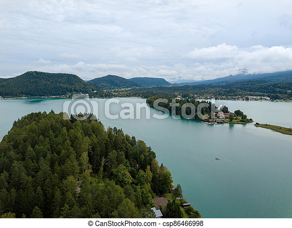 Aerial view on Lake 'Faaker See' in Carinthia (Kaernten), Austria with its famous turquoise water on a cloudy summer day - csp86466998