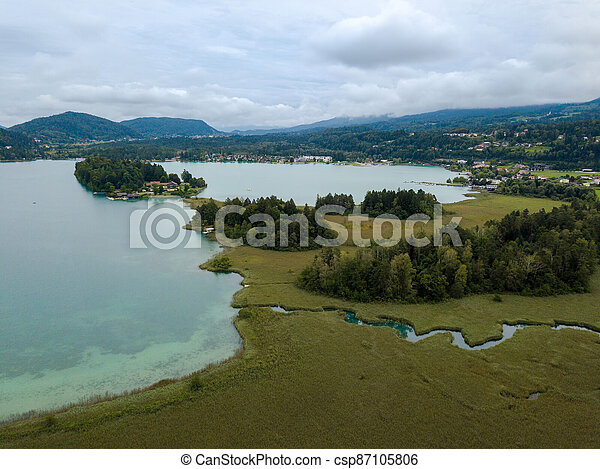 Aerial view on Lake 'Faaker See' in Carinthia (Kaernten), Austria with its famous turquoise water on a cloudy summer day - csp87105806