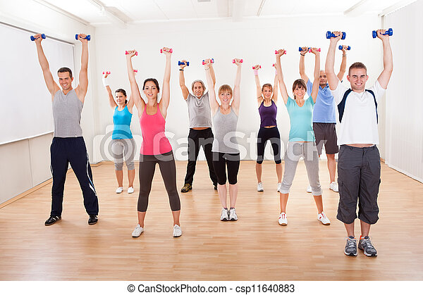 Aerobics class working out with dumbbells - csp11640883