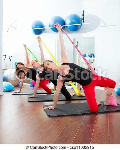 Aerobics pilates women with rubber bands in a row - csp11002915