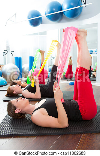 Aerobics pilates women with rubber bands in a row - csp11002683