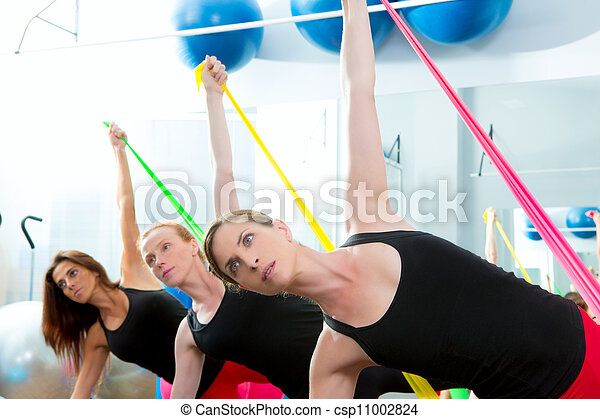 Aerobics pilates women with rubber bands in a row - csp11002824