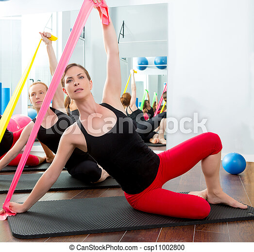 Aerobics pilates women with rubber bands in a row - csp11002800