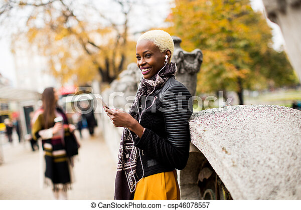 African american and caucasian woman posing outside with mobile phone and a cup of coffee to go in autumn - csp46078557