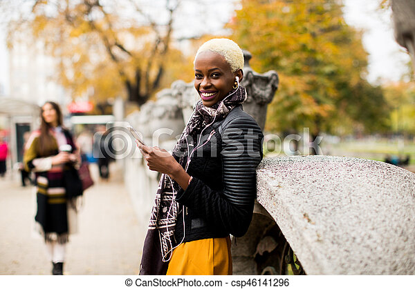 African american and caucasian woman posing outside with mobile phone and a cup of coffee to go in autumn - csp46141296